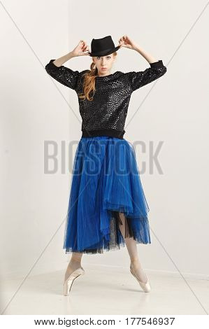 Sweet hipster ballerina in a tutu pointe shoes and glasses dancing with hat. Modern dance. Youth culture