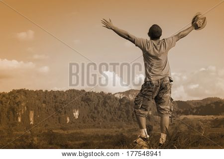 Man Asian is happy with nature  view.Man show his hand and relax.Tone