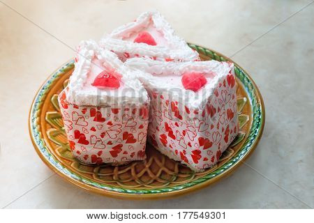 On the table in a ceramic plate are three pieces of cakes Packed in beautiful paper.