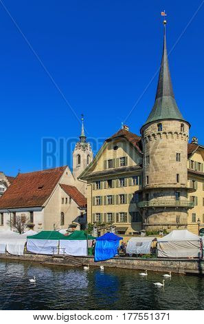Lucerne, Switzerland - 7 May, 2016: historic buildings and street market tents along the Reuss river. Lucerne is a city in central Switzerland, it is the capital of the Swiss canton of Lucerne and the capital of the district of the same name.