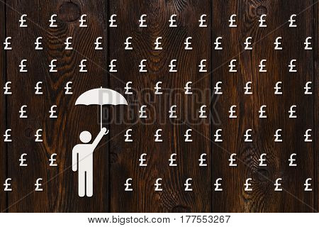 Paper man with umbrella standing in rain of pound sterlings money concept abstract conceptual image