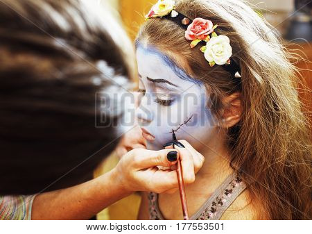 little cute child making facepaint on birthday party, zombie Apocalypse facepainting, halloween preparing concept at home
