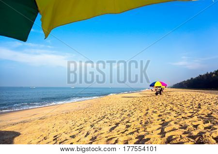 Relax On The Beach Under Umbrellas In The Shade. Beach Chairs On The White Sand Beach With Cloudy Bl