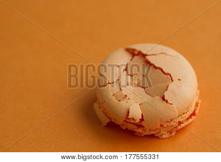 Orange single crushed macaroon over orange background with copy space soft focus