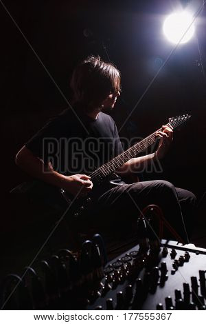 young guitarist play on the electric guitar
