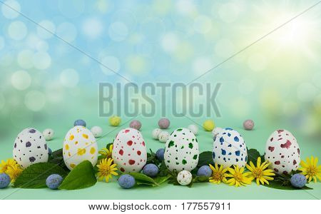 Row of painted speckled chocolate eggs isolated on green background with leaves and flowers
