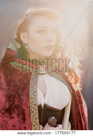 Warrior woman with sword in medieval clothes shines in sunlight