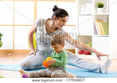 Sportive woman is engaged in fitness and yoga at home. Her son kid by near sitting and playing.