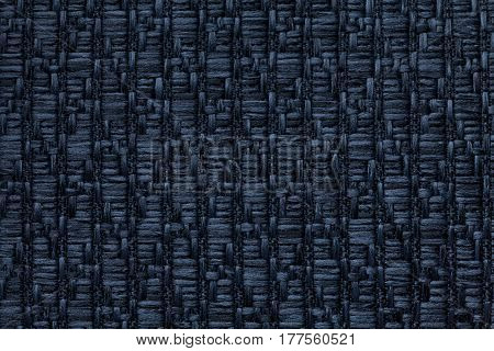 Navy blue knitted woolen background with a pattern of soft fleecy cloth. Texture of denim textile closeup.
