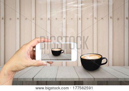 Woman hand holding and using mobilecell phonesmart phone photography and redolent cappuccino coffee on wooden floor with wooden background.