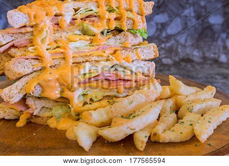 Sandwich with spicy sauce and French fries on wood plate.