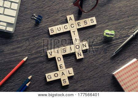 Success and other related words in crossword on wooden table