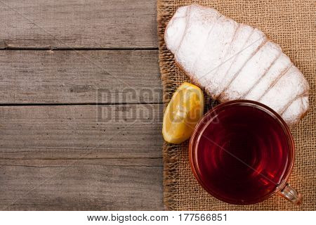 Cup of tea with croissant sprinkled with powdered sugar on old wooden background with copy space for your text. Top view.