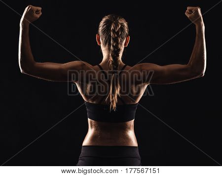 Studio shot of a fit young woman showing her muscles, against a dark background