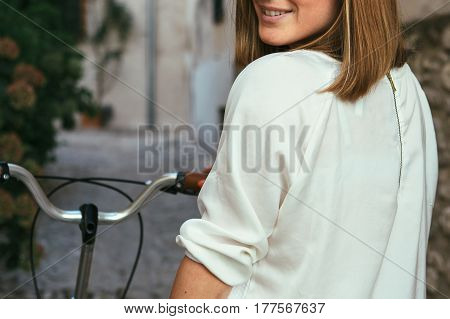 Crop shot of young female on bicycle and smiling over shoulder.