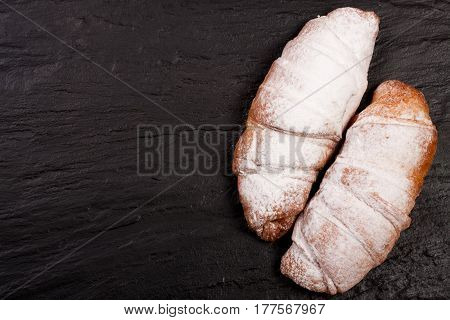 two croissants sprinkled with powdered sugar on black stone background with copy space for your text. Top view.