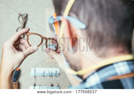 Man holding wooden glasses being in process of their manufacture.