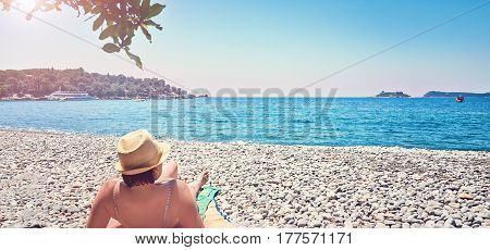 Woman sunbathes tanning beach  Zanjic Adriatik sea Montenegro  peninsula Lustica.
