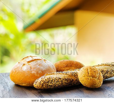 Fresh Bread On Black Wooden Table On Rural Landscape Background