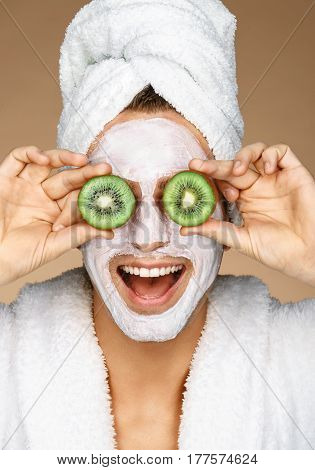 Funny young man with facial mask and pieces of kiwis on eyes. Photo of well groomed man receiving spa treatments. Beauty & Skin care concept