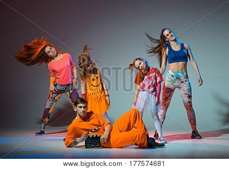 Group of man, woman and teens dancing hip hop choreography and posing at studio on gray