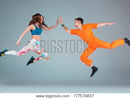 The man, woman jumping and dancing hip hop choreography and posing at studio on gray