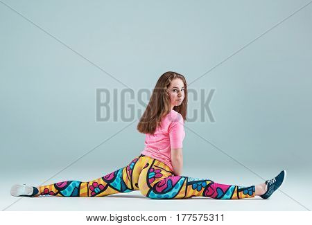 The teen girl dancing hip hop choreography and posing at studio on gray