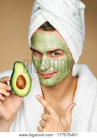 Man wearing towel and facial mask of avocado. Photo of well groomed man receiving spa treatments. Beauty & Skin care concept