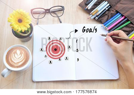 hand writing goals memo list on a notebook with cup of coffee on wooden desk.