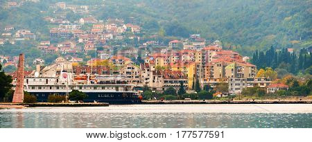 Kotor riviera. Liner moored at the shore, Montenegro with old town at the background