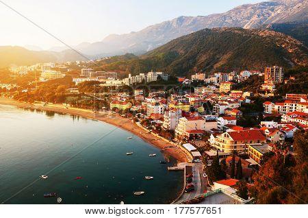 Montenegro at sunset. Aerial view of coastal town Rafailovici, Budvanska Riviera, Montenegro. Adriatic resort with beach and sea in the evening