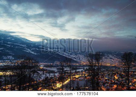 Liechtenstein in winter. Aerial view of Vaduz, Liechtenstein at night, illuminated streets with colorful sunset sky over the mountains.