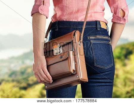 Young Woman In Deep Blue Jeans Holding A Bag