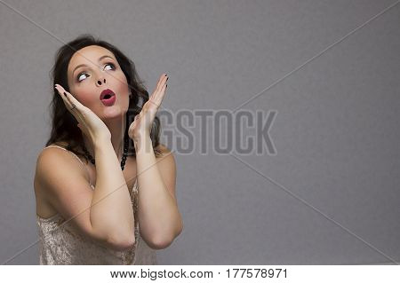 Excited young woman with open palms. Horizontal studio shot. Copy space