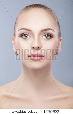 portrait of young beautiful woman with blue eyes  on blue background. everyday makeup