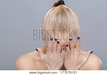 beautiful blonde girl covers her face with her hands. despair