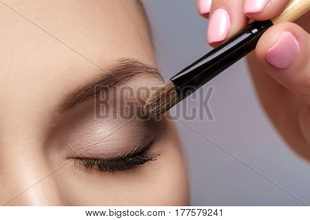 makeup artist apply makeup brush for eyes. makeup for a young beautiful girl. brown eye shadow. close up