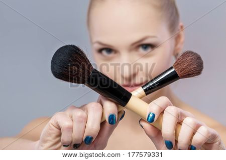 beautiful woman with natural make-up holding a make-up brush. the brush is sharp and the blurred girl