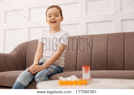 Feeling good. Happy smiling sweet girl looking at the set of pills standing on the table and being delighted for not having to take them