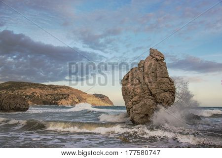 Illuminated with evening sun Aphrodite's Rock (Petra tou Romiou or Rock of the Greek - Cyprus) in raging sea. Blue sky with clouds in background.