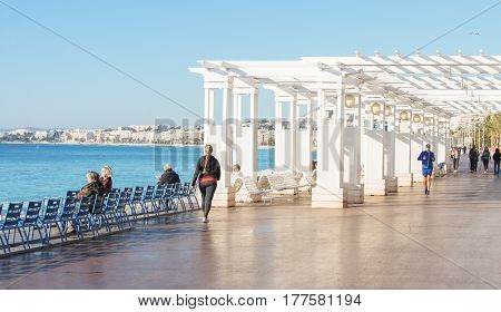 Nice, France - 25 February, People on the waterfront of Nice, 25 February, 2017. People and tourists having a rest on the Cote d'Azur.