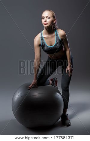 beautiful blonde girl in sports clothes sitting on a fitness ball on a dark background