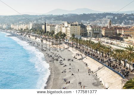 Nice, France - 25 February, People on the spring embankment of Nice, 25 February, 2017. Panoramic view of houses and streets of Nice.