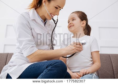 No worries. Cute clever smiling doctor and her patient having fun together while doing some tests and going through a general health checkup