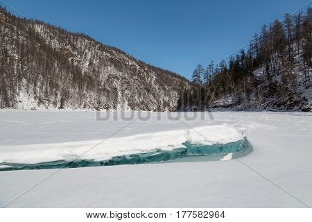 Winter landscape with frozen river and ice floe in the foreground South Yakutia Russia