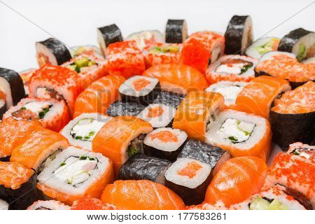 Salmon sushi and rolls - japanese food restaurant delivery, closeup of platter set isolated at white background