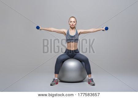 beautiful blonde girl in sportswear does exercises with dumbbells on the fitness ball on a grey background