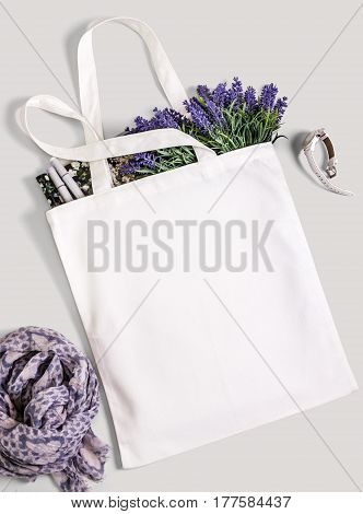 White blank cotton eco tote bag with lavender flowers magazine watches and scarf. Design mockup.