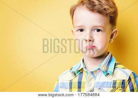 Portrait of a cute little funny boy looking at camera. Yellow background. Copy space. Children fashion, summer concept.