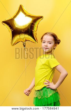Portrait of a cute happy girl in bright summer clothes with a balloon over yellow background. Happy childhood. Copy space.